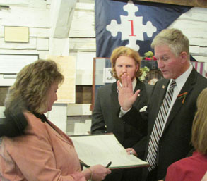 man hold up hand and read oath of office with woman holding a book