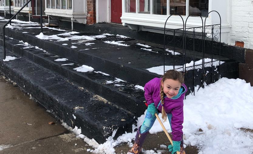 girl shovels snow on village sidewalk