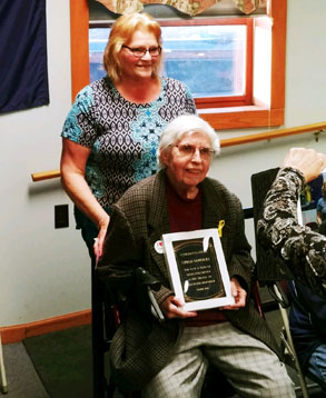 woman in wheelchair holding large plaque