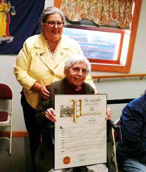 woman in wheelchair holds large plaque