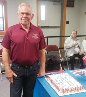 man standing next to cake