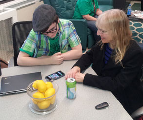 teen works on a smart phone with a senior citizen