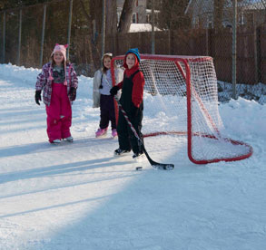 children play hockey on ice rink