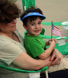 little boy wave American flag in woman's arms