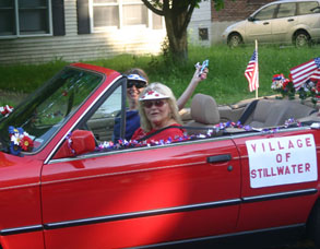 woman waves from red convertible