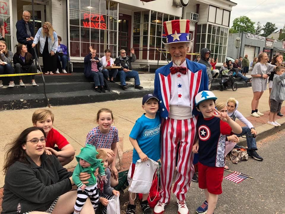 children sit with Uncle Sam waiting for parade
