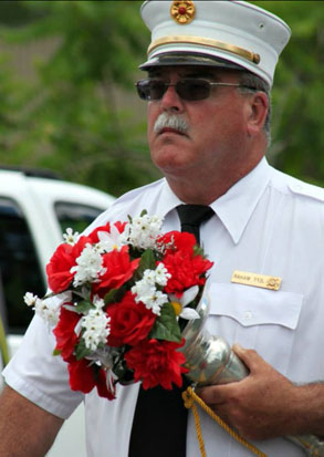 fireman marches in parade carrying flowers