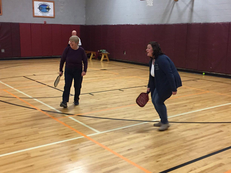 two women play pickleball