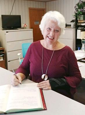 gray hair woman sign a book