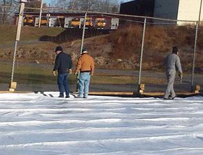 men prepare the ice skating rink