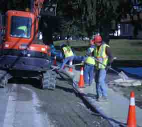 crews work on sidewalk repairs