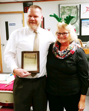 man holds up plaque with woman in reindeer ears next to him