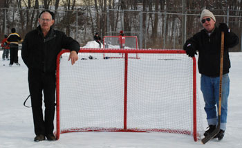 two men stand near hockey goal on the ice