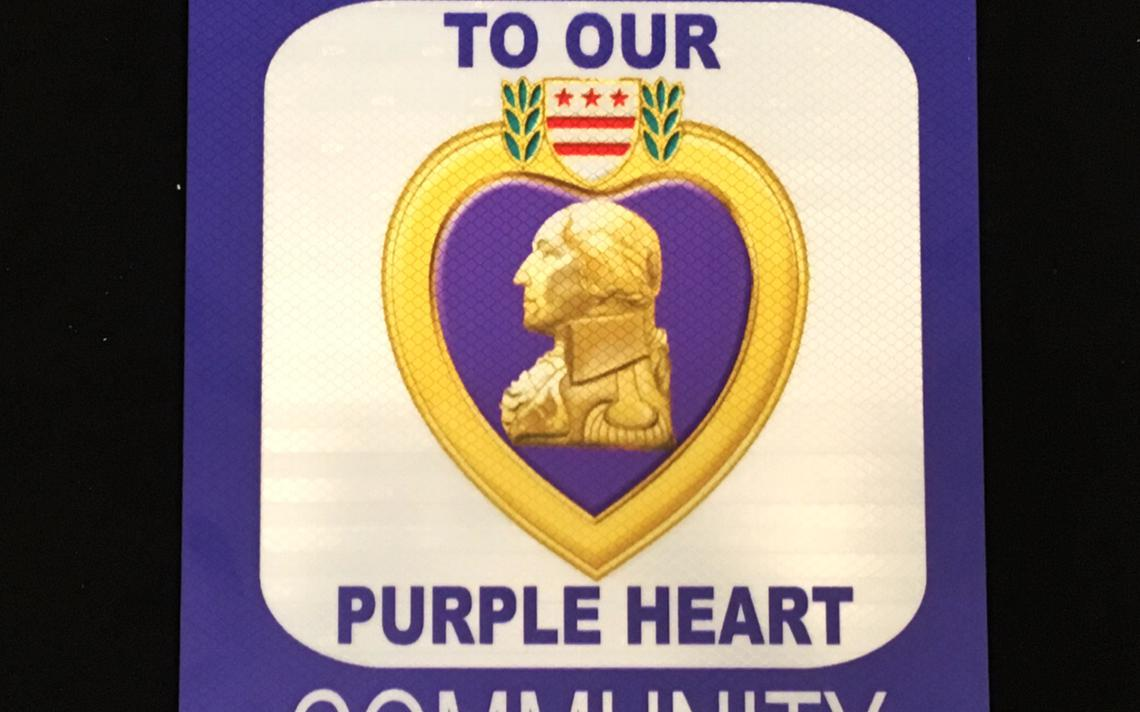 sign with a purple heart logo and the words To Our Purple Heart Community