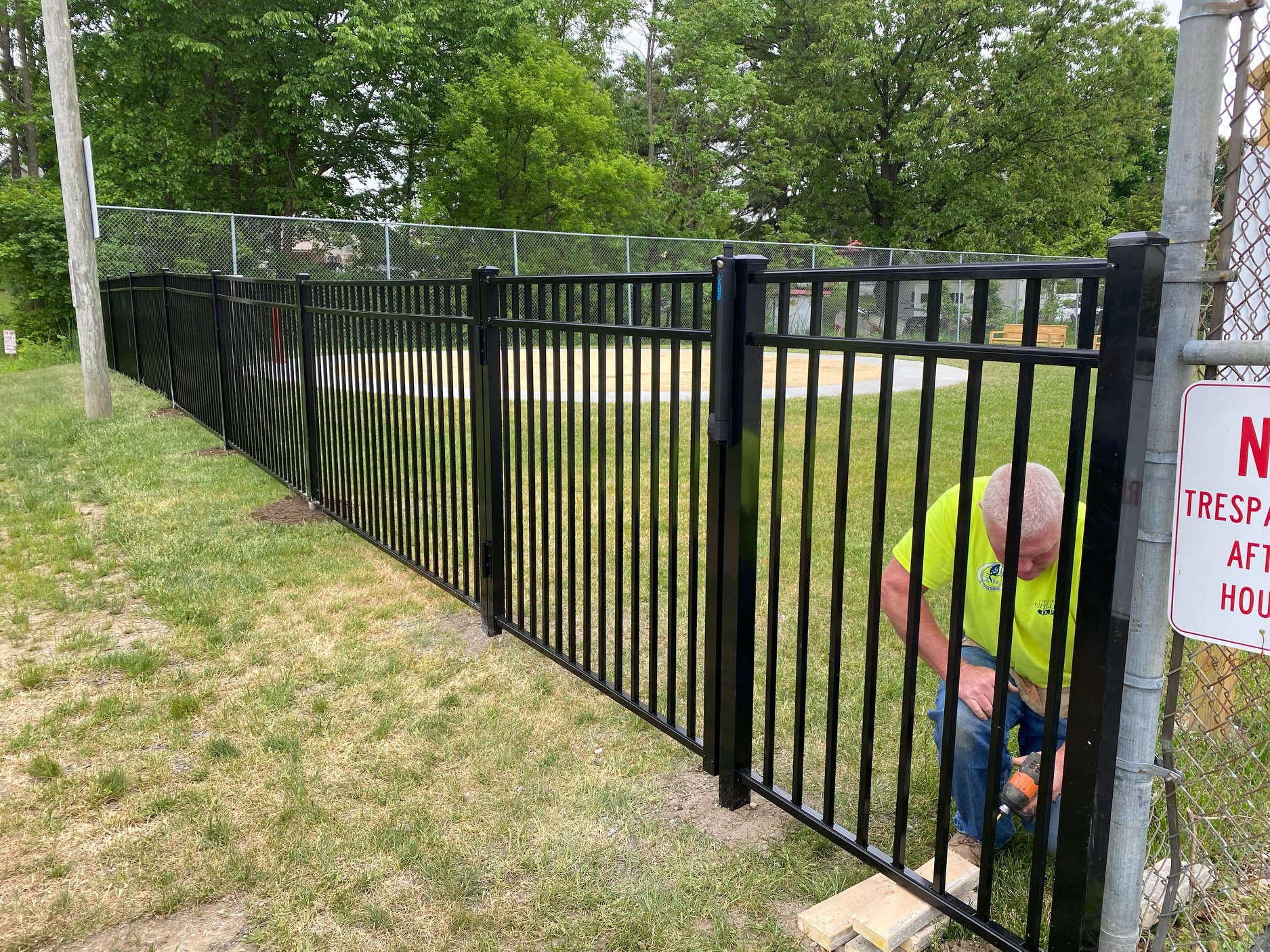 man installs a black fence