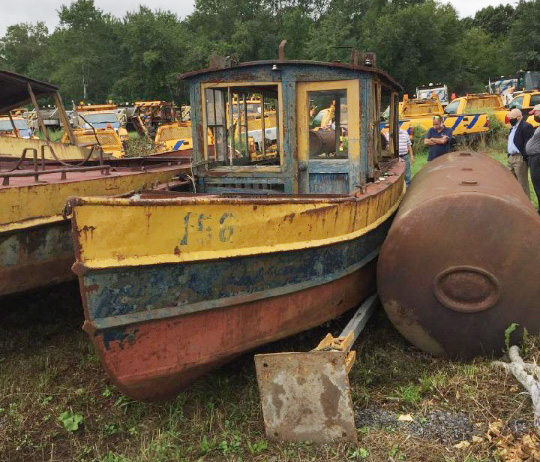 old yellow boat docked in a scrap yard