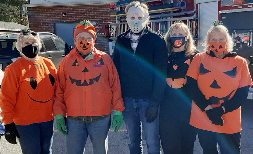 five village trustees dressed as pumpkins for Halloween