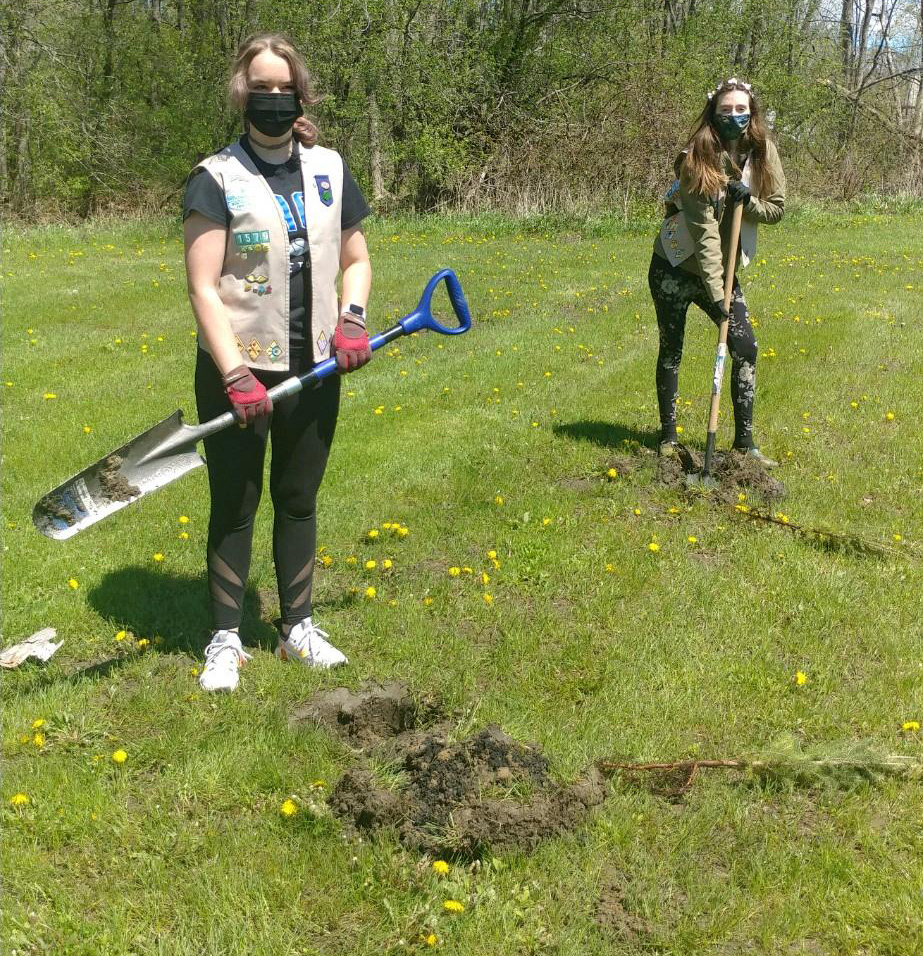 two girls scouts plant trees in a park