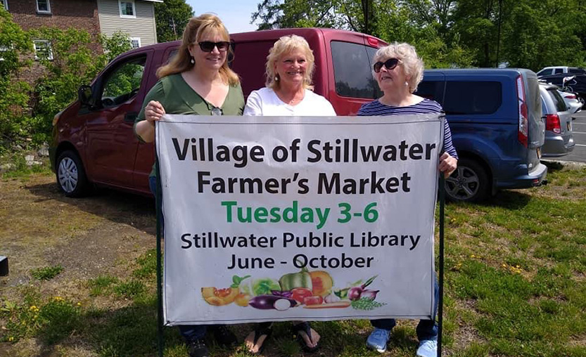 three women in front of a farmer's market sign